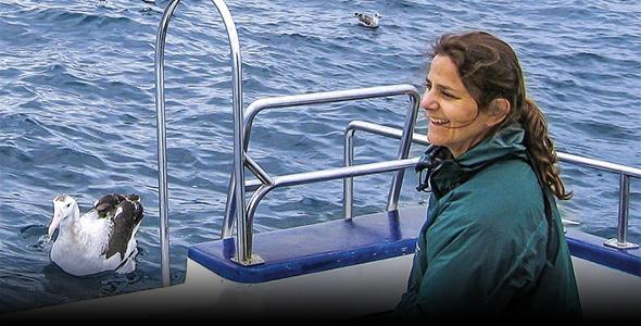 Myra Finkelstein sits in a boat with an albatross nearby