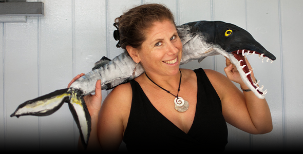 Stacy Jupiter poses with a puppet used in a show she staged for kids about how to protect fish, photo credit Rebecca Weeks