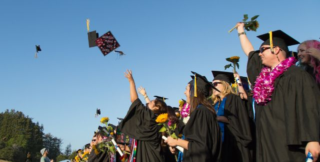 Image of UC Santa Cruz graduates happily hurling their mortarboards into the sky