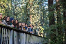 Students lined up, smiling towards the camera, on one of UC Santa Cruz's pedestrian bridges